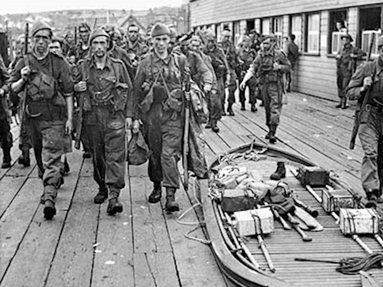 commandos_marching_past_a_collapsed_goatley_boat_in_world_war_two