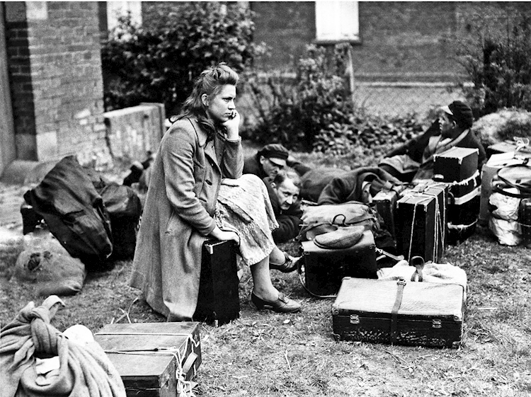 a_woman_sits_on_a_suitcase_after_being_liberated_from_a_german_prison_camp_photo_from_mirrorpix